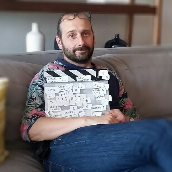 Normal on sofa with clapperboard